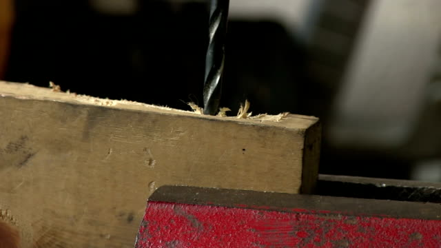 closeup power drill into wood in red vice with sound video
