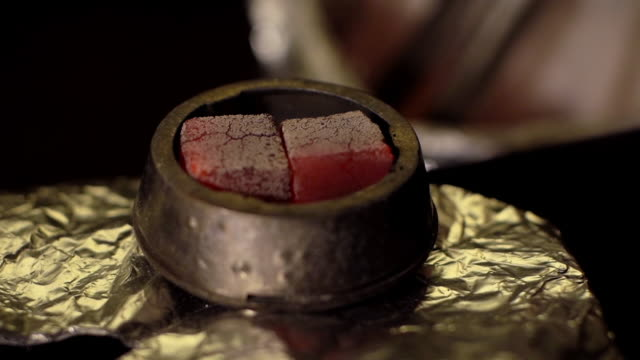 Close-up preparation of a bowl for a hookah in slow motion