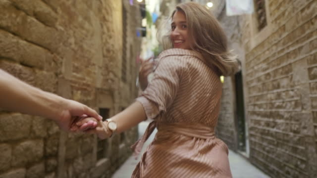 nahaufnahme hübsche frau hält mann hand. pov der flirtenden frau ruft mann - hinter stock-videos und b-roll-filmmaterial
