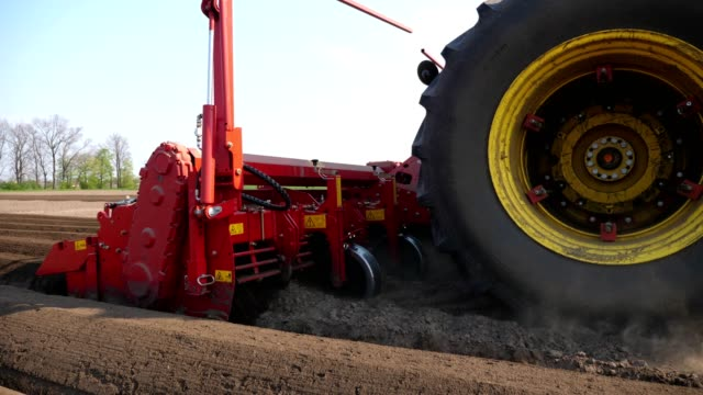 close-up, process of mechanized machine potatoe planting. large tractor with special equipment makes Long flat top rows, furrows, mounds, for newly planted potatoes on plowed black soil field, spring day, planting season - vídeo