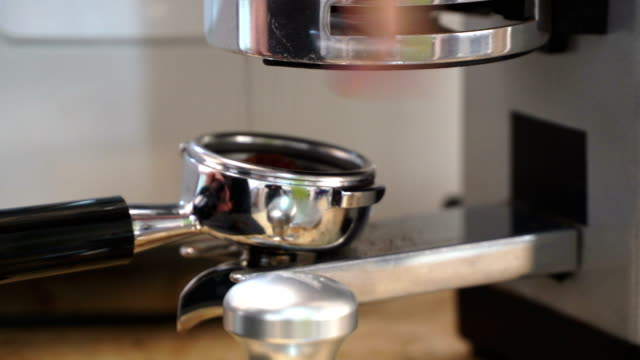 Close-up professional grinding and manual pour to holder freshly roasted coffee for espresso machine. Barista preparing coffee in a coffee shop. Concept of coffee making, service, catering video