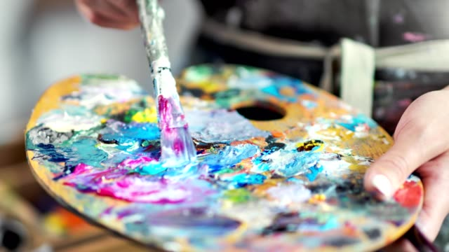 close-up professional painter hands mixing color paint on palette creating amazing picture - tavolozza video stock e b–roll