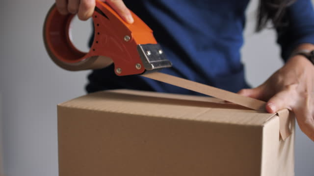 Close-up Professional Warehouse Worker Finishes Order, Sealing Cardboard Boxes Ready for Shipment