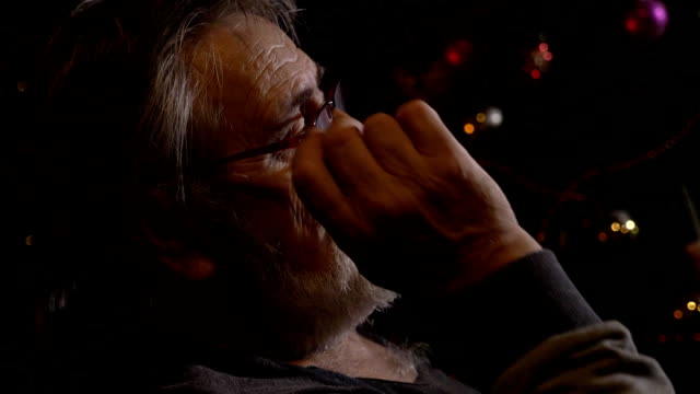 Close-up profile portrait of tired senior man takes off his glasses at dark room video