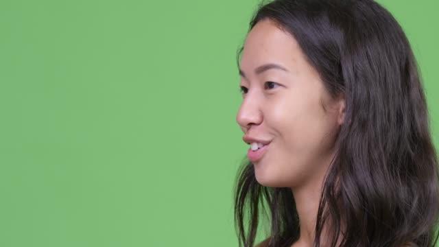インタビューを受けている幸せな若い美しい多民族女性のクローズアッププロフィールビュー - スタジオ 日本人点の映像素材/bロール