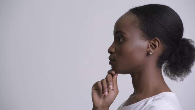 closeup profile view of young beautiful african woman thinking - афро стоковые видео и кадры b-roll