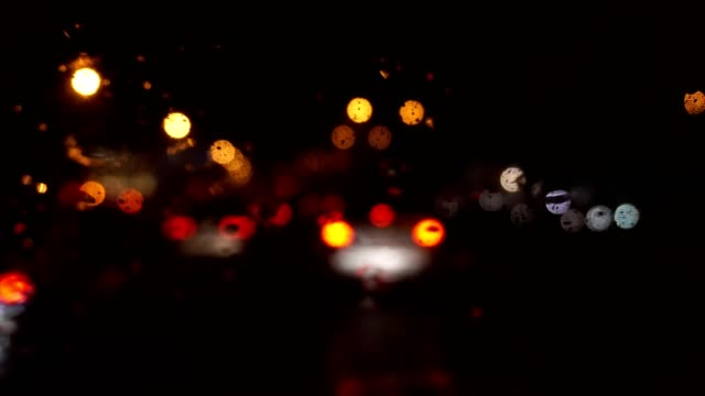 Closeup Rain Water Drops on Car Window Glass in Rainy Day with Blurred Night City Traffic as Background video