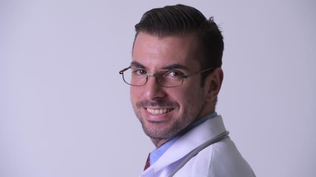 närbild bakifrån av happy young hispanic man doctor med glasögon - hospital studio bildbanksvideor och videomaterial från bakom kulisserna