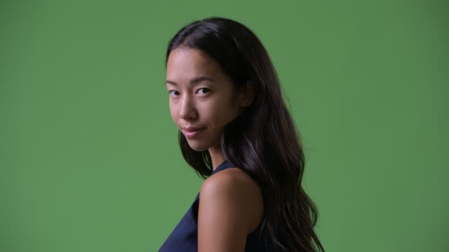 Closeup rear view of young beautiful multi-ethnic businesswoman looking back Studio shot of young beautiful multi-ethnic businesswoman against chroma key with green background low lighting stock videos & royalty-free footage