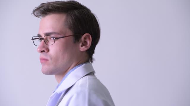 närbild bakifrån av unga stilig man läkare med glasögon vrida runt - hospital studio bildbanksvideor och videomaterial från bakom kulisserna