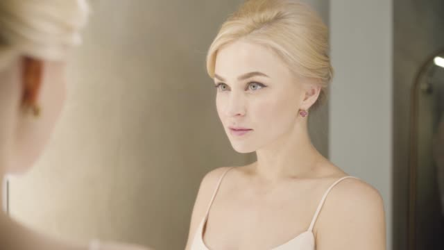 Close-up reflection of beautiful blond Caucasian woman with grey eyes looking at mirror and smiling. Attractive young girl posing indoors. Backstage, fashion, elegance.