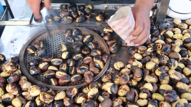 Close-up roasting delicious chestnuts on the grill. Turkish street food, chestnut kebab. Istanbul streets and traditional foods.