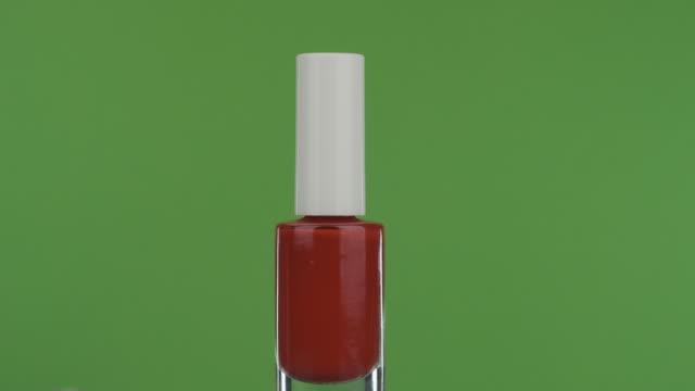 närbild, rotation av rött nagellack, på en grön skärm. - nagellack bildbanksvideor och videomaterial från bakom kulisserna