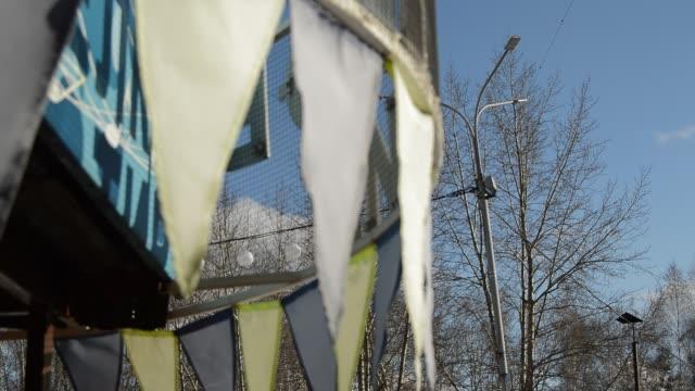 närbild, selektiv fokus, vinden slår kransar av färgglada flaggor mot blå himmel, park under våren - lucia bildbanksvideor och videomaterial från bakom kulisserna