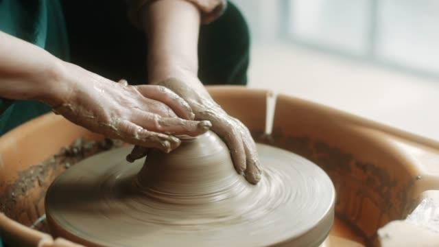 vídeos de stock, filmes e b-roll de close-up, sênior mulher usando a roda de oleiro no atelier - cerâmica artesanato