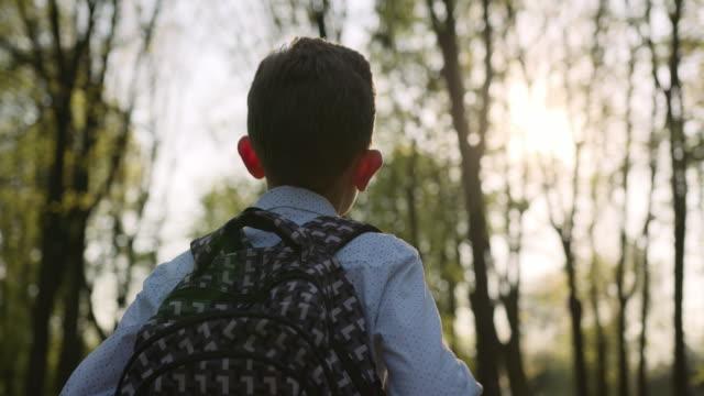 stockvideo's en b-roll-footage met close-up shoot. een jongen loopt door het park met een rugzak. schieten van achteren. 4k - schooljongen