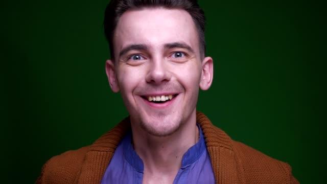 närbild shoot of adult attraktiv man är upphetsad och överraskade leende glatt tittar på kamera med bakgrund isolerade på grön - male eyes bildbanksvideor och videomaterial från bakom kulisserna