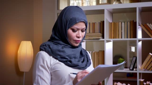 stockvideo's en b-roll-footage met close-up shoot van volwassen moslim zakenvrouw het bestuderen van de grafiek in de bibliotheek en op zoek naar een oplossing voor probleem op de werkplek binnenshuis - perzische golfstaten