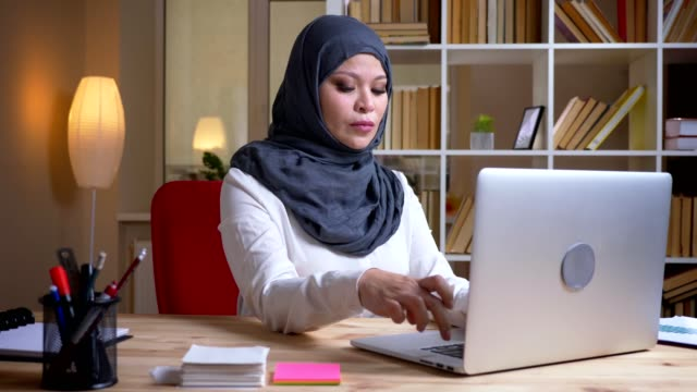 closeup shoot of adult muslim busy businesswoman in hijab working on the laptop on the workplace indoors - libia video stock e b–roll