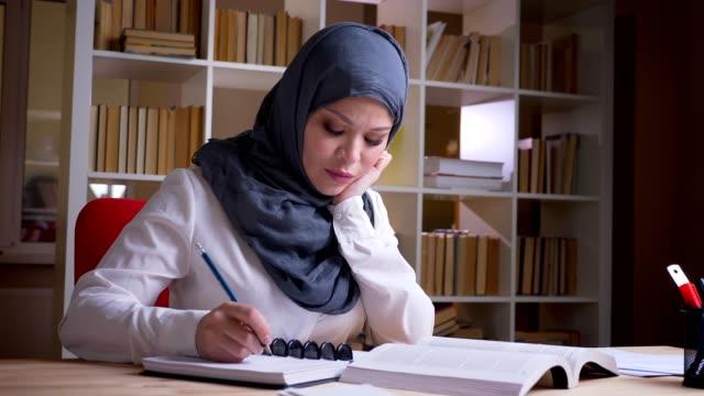 närbild skjuta av vuxna muslimska kvinnliga studenten i hijab få en medicinsk utbildning som studerar för en medicinsk examen i biblioteket inomhus - anständig klädsel bildbanksvideor och videomaterial från bakom kulisserna