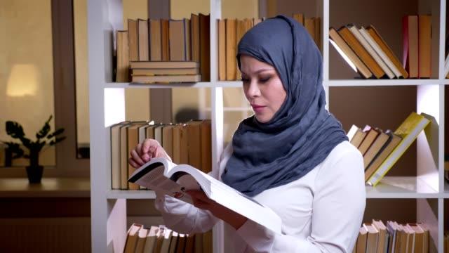 närbild skjuta av vuxna muslimska kvinnliga studenten i hijab läsa en bok få en medicinsk utbildning som står i biblioteket inomhus - anständig klädsel bildbanksvideor och videomaterial från bakom kulisserna