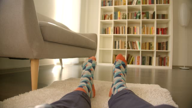 closeup shoot of cameramen legs sitting on the floor on the carpet being relaxed with bookshelves on the background - носок стоковые видео и кадры b-roll