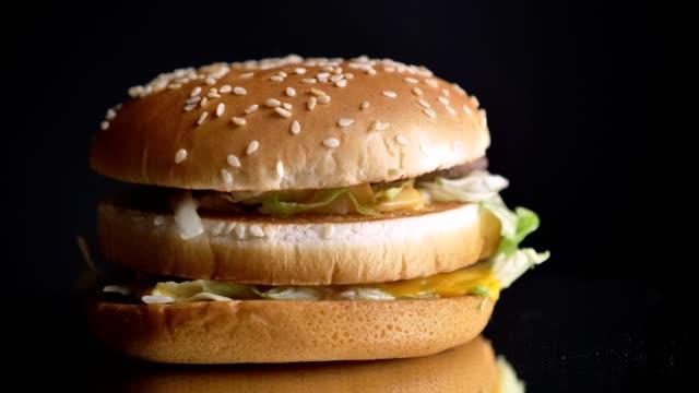 근접 촬영의 육즙이 더블 치즈 버거 맛 있는 패티 양상추와 참 깨에 빵 - burger and chicken 스톡 비디오 및 b-롤 화면