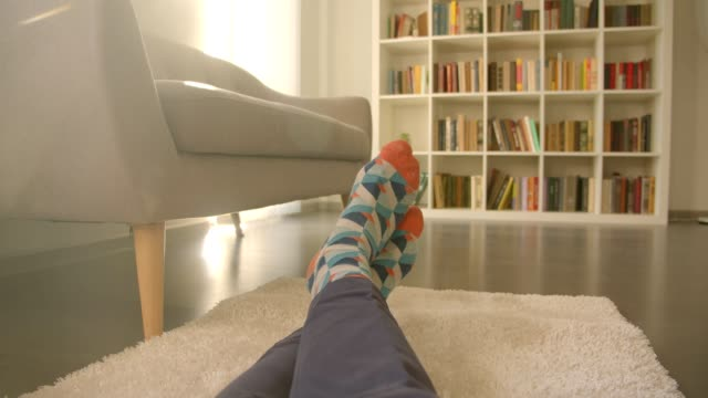 closeup shoot of male legs sitting laidback on the floor on the carpet being relaxed with bookshelves on the background - calzino video stock e b–roll