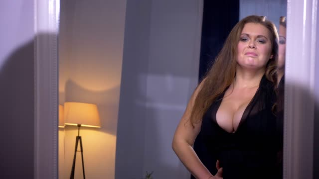 vidéos et rushes de gros plan shoot de dodu sexy jolie caucasienne femelle avec gros seins regardant elle-même heureusement à l'intérieur dans un appartement confortable - décolleté