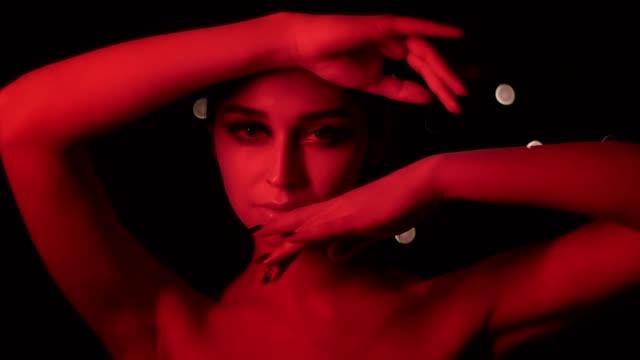 stockvideo's en b-roll-footage met close-up schieten van mooie sexy vrouw met verbluffende make-up met rode neon licht en bokeh achtergrond poseren in de voorkant van de camera - drag queen