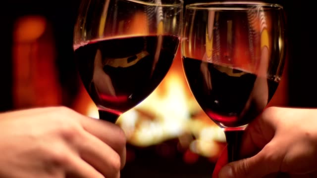 Closeup shoot of two hands of friends clinking glasses with red wine celebrating with cozy warm fireplace on the background indoors in the evening