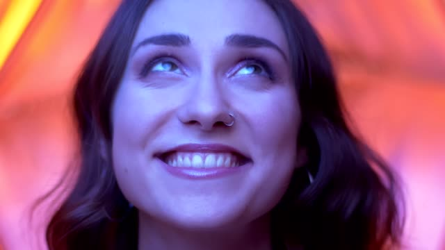 Closeup shoot of young attractive caucasian female face with pretty eyes looking at camera with neon red background