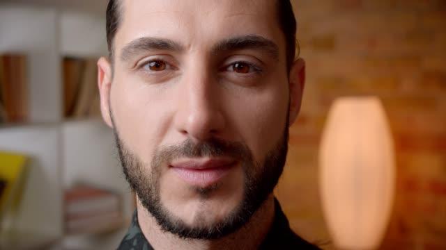 primo piano scatto di giovane attraente volto maschile barbuto musulmano guardando la telecamera all'interno - cultura del medio oriente video stock e b–roll