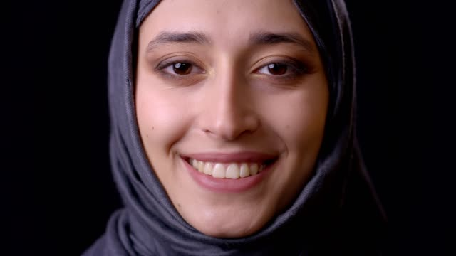 closeup shoot of young attractive muslim female face in hijab looking at camera with smiling facial expression with background isolated on black - ислам стоковые видео и кадры b-roll