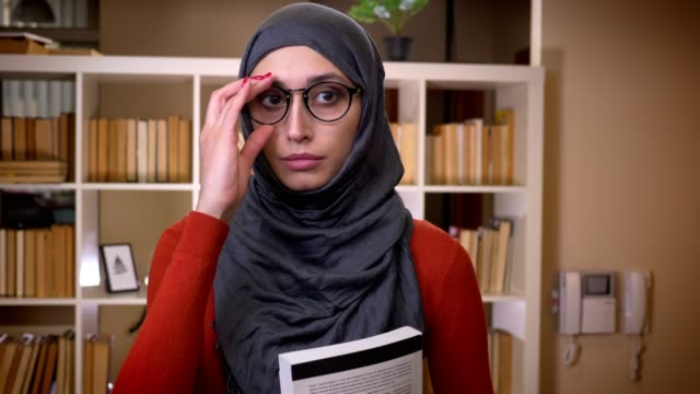 closeup shoot of young attractive muslim female student in hijab fixing her glasses and holding a book standing indoors and looking straight at camera in the library university - abbigliamento religioso video stock e b–roll