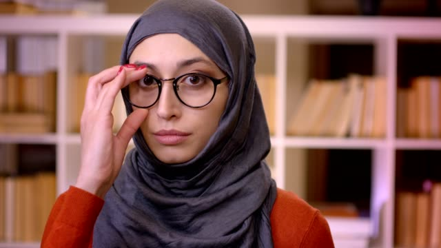 closeup shoot of young attractive muslim successful female student in hijab fixing her glasses looking at camera standing indoors in the library - abbigliamento religioso video stock e b–roll