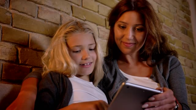 Closeup shoot of young caucasian mother and her small pretty girl using the tablet together while sitting on the couch indoors at home