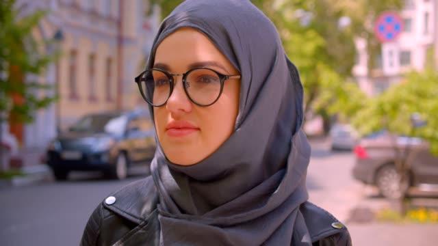 primo piano scatto di giovane bella donna musulmana in hijab e occhiali sorridenti felicemente guardando la macchina fotografica nella città urbana all'aperto - libia video stock e b–roll