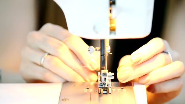 Close-up shooting hands putting pink thread in sewing machine video