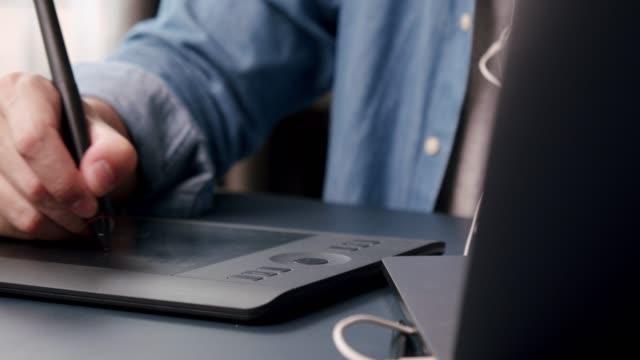vídeos de stock, filmes e b-roll de close-up shot 4k resolução homem asiático designer gráfico mão desenhando seu trabalho de ilustração em laptop com tablet gráfico no home office enquanto coronavirus ou covid-19 situação de bloqueios. trabalhar em casa, trabalhar remotamente conc - designer profissional