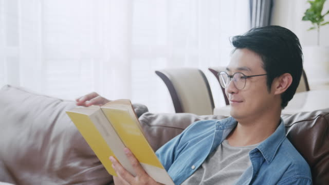 Close-up shot POV Asian man reading a book in the living room. Adult male studying history on Analog book while sitting on a sofa. Learning, knowledge, education, relaxing in daily life activities