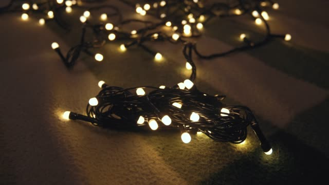 Close-up shot hank of christmas garland with golden lights on a playd. Christmas concept. Home decor