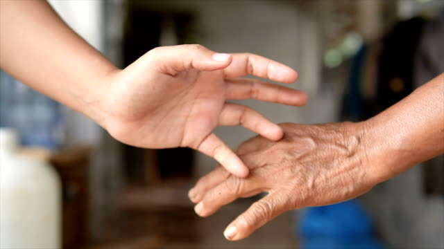 close-up shot little finger hand of the girl and old woman be hand in hand, metaphor contract commitment, and promise, selective focus shallow depth of field - mano donna dita unite video stock e b–roll