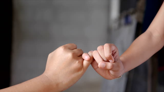 close-up shot little finger hand of the girl and young woman be hand in hand, metaphor contract commitment, and promise, selective focus shallow depth of field - mano donna dita unite video stock e b–roll