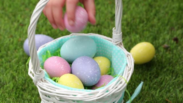 Close-up shot little girl putting Easter eggs into basket