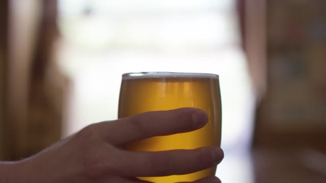 Close-Up Shot of a Bartender Handing a Beer to Someone Else Across a Bar Counter A Caucasian man's hand appears in the shot and picks up a frothy glass of beer at a bar. gripping stock videos & royalty-free footage