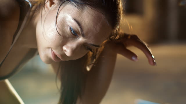close-up shot of a beautiful athletic woman wipes sweat from her forehead with a hand, looks into camera. she's tired after intensive cross fitness exercise. - sport filmów i materiałów b-roll