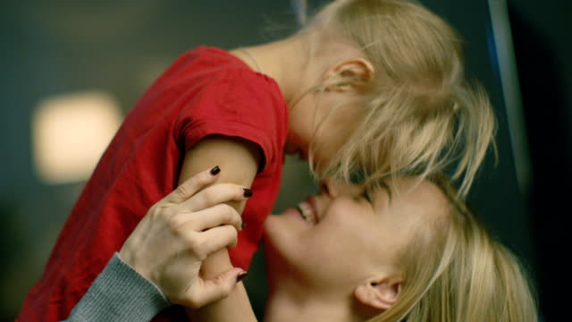 Close-up Shot of a Beautiful Mother Holding Her Cute Blonde Daughter and Smiling. - vídeo