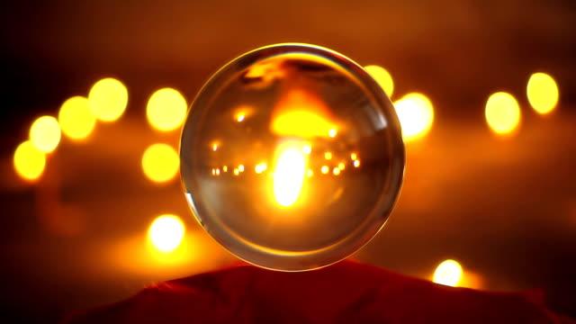 vidéos et rushes de closeup shot d'une bougie à l'intérieur d'une boule de cristal - charmeur