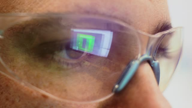 close-up shot of a caucasian technician's eye with the reflection of a computer screen in his protective eyewear in an indoor office - occhiali protettivi video stock e b–roll